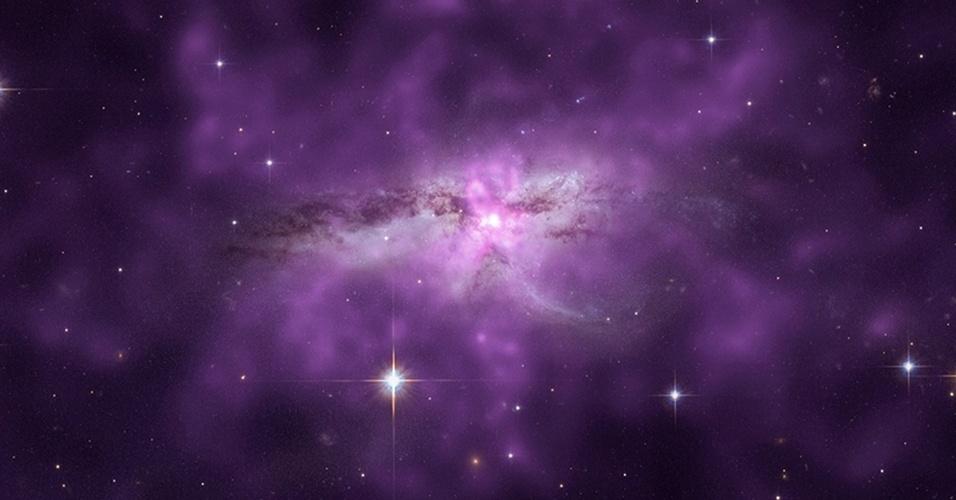 """30.abr.2013 - Duas galáxias espirais em processo de fusão estão cercadas por uma nuvem colossal de gás quente, mostra estudo da Nasa (Agência Espacial Norte-Americana). O halo gasoso do sistema NGC 6240 é tão poderoso que se estende por mais de 300 mil anos-luz e pesa 10 bilhões de vezes a massa do nosso Sol. Os violentos choques que ocorrem entre as próprias galáxias expulsam o gás de cada uma para fora, criando uma bolha de gás quente ao redor. Além disso, sugerem os astrônomos, uma explosão de formação de estrelas, que durou ao menos 200 milhões de anos, também pode ser a origem dessa gigantesca nuvem no espaço. A supernova enriqueceu os gases quentes com o arremesso de grandes quantidades de oxigênio, magnésio e silício, o que a ajudou a nuvem a se expandir calmamente até se misturar ao gases mais gelados que já existiam por lá. O estudo, que foi publicado no periódico """"Astrophysical Journal"""", combina a visão de raios x do observatório Chandra, da Nasa, com a do campo visível do telescópio Hubble"""