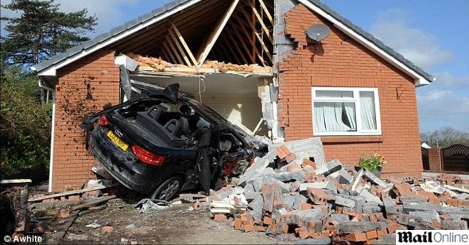 """30.abr.2013 - O motorista de um Audi A3 perdeu o controle do veículo e bateu contra a parede de uma casa na cidade de Swansea, no País de Gales (Reino Unido). O acidente destruiu parte da sala de estar da casa. A proprietária, uma mulher de 72 anos, disse ao jornal britânico """"Daily Mail"""" que ela estava no coômodo momentos antes do acidente. O motorista foi levado a um hospital por equipes de socorro"""