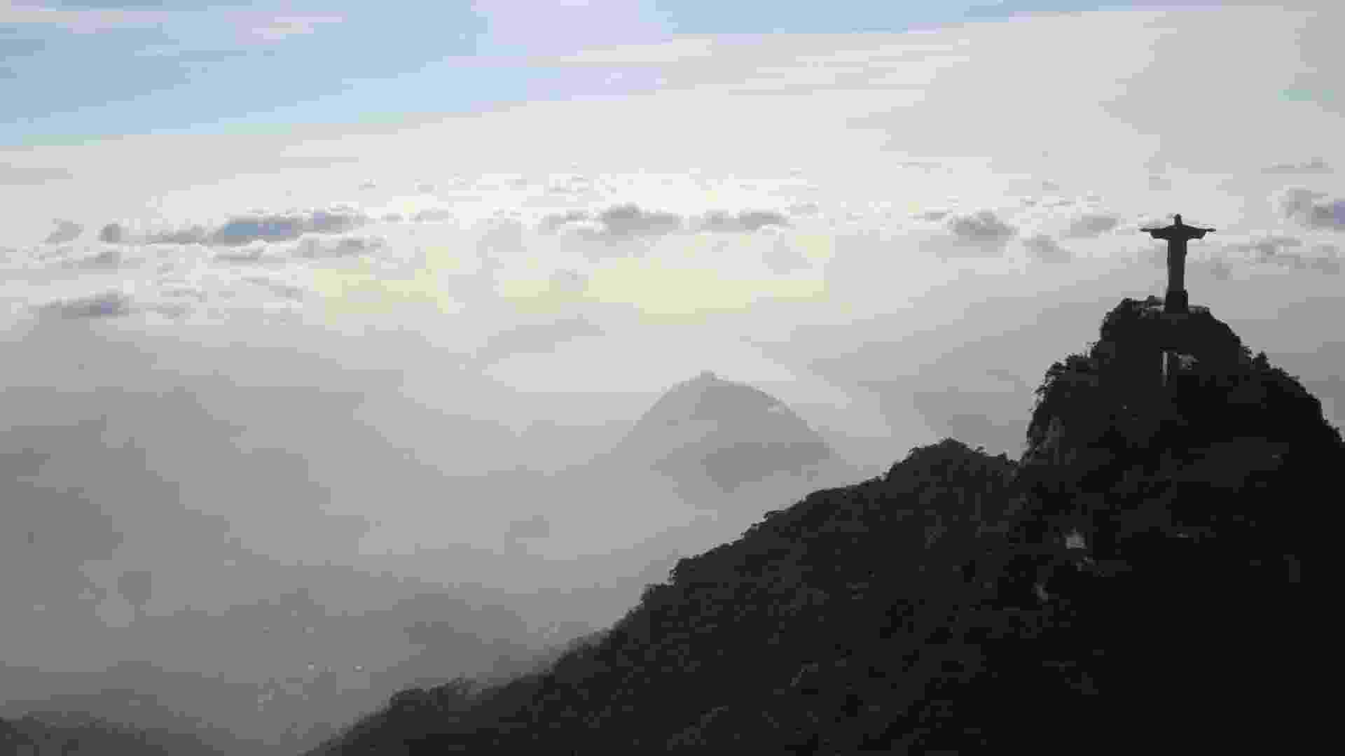 2.mai.2013 - O estátua do Cristo Redentor, no Rio de Janeiro, é visto sobre nuvens nesta quinta-feira (2). Por causa do forte nevoeiro que encobriu a cidade nesta manhã, o aeroporto Santos Dumont ficou fechado para pousos durante duas horas - Carlos Eduardo Cardoso/Agência O Dia/Estadão Conteúdo
