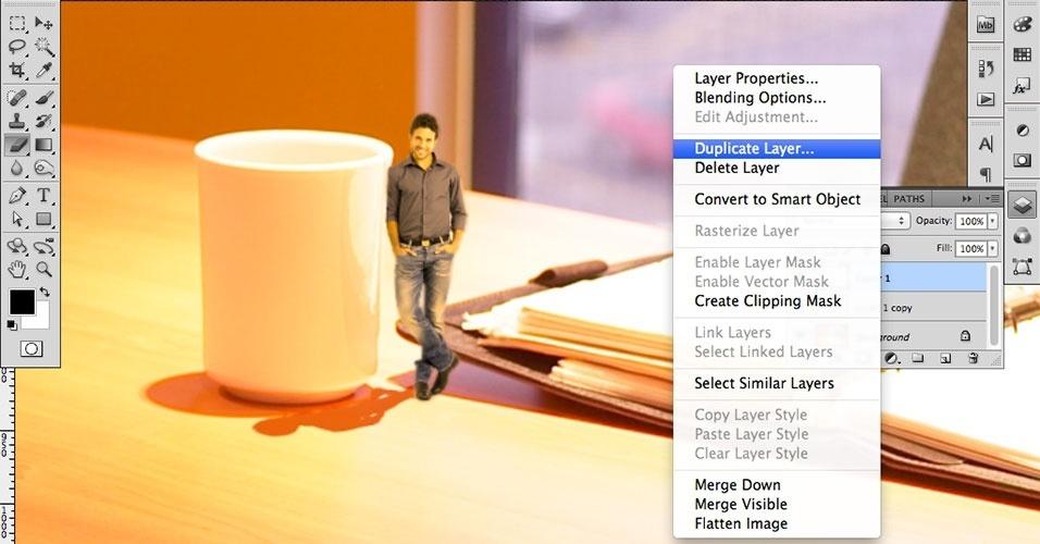 Próximo passo: reflexos. Note que a xícara produz reflexos e que nosso modelo está colado a ela -- portanto, ele seria refletido se a foto fosse real. Vamos então criar esse efeito. Para começar, duplique a camada, clicando com o botão direito sobre a camada da pessoa e depois em Duplicate Layer (Duplicar Camada)