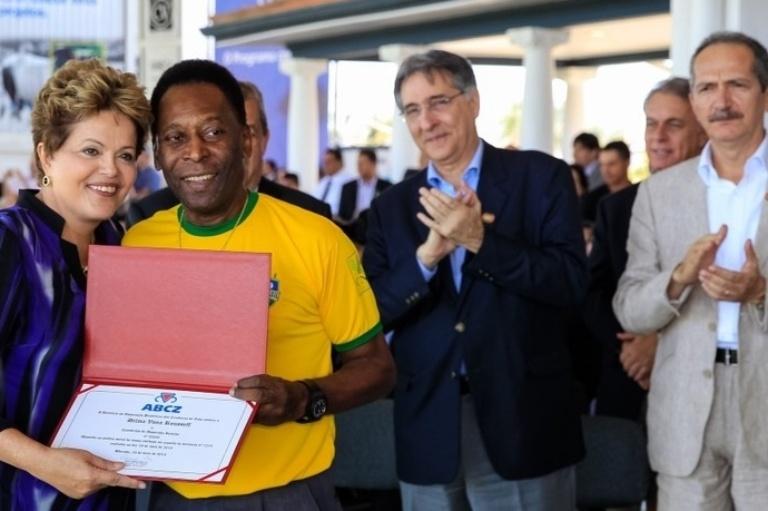 3.mai.2013 - A presidenta Dilma Rousseff recebe de Pelé o título de sócia da ABCZ (Associação Brasileira dos Criadores de Zebu) durante abertura oficial da 79ª Expozebu 2013 (Exposição Internacional de Gado Zebu), no parque Fernando Costa, em Uberaba (MG). Ao fundo, o ministro do Desenvolvimento, Fernando Pimentel, e o ministro do Esporte, Aldo Rebelo
