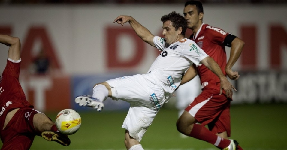 04.mai.2013 - Meia argentino Montillo, do Santos, é travado por zagueiro do Mogi Mirim ao tentar chute ao gol