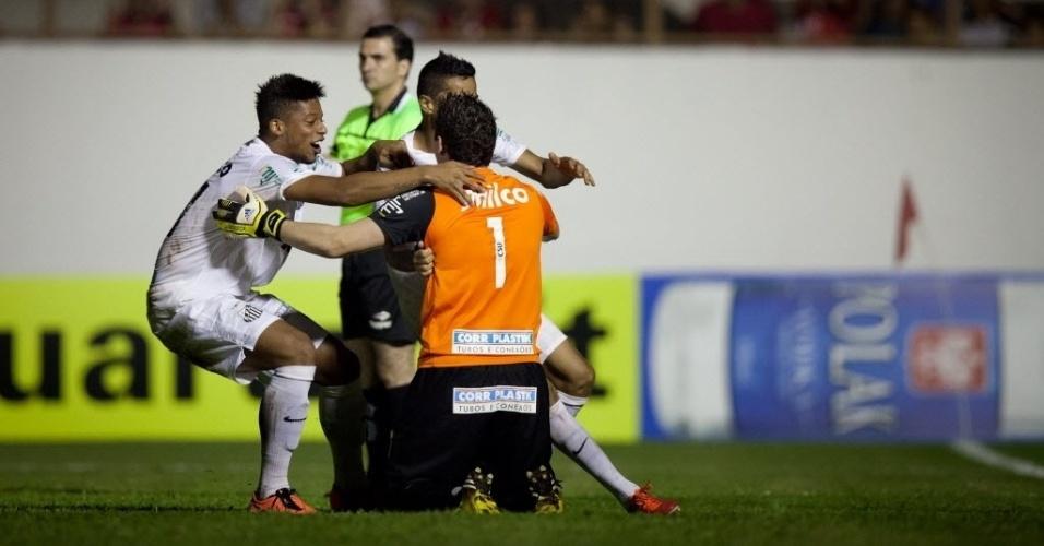 04.mai.2013 - Rafael, goleiro do Santos, é abraçado pelos companheiros após pegar o pênalti decisivo contra o Mogi Mirim