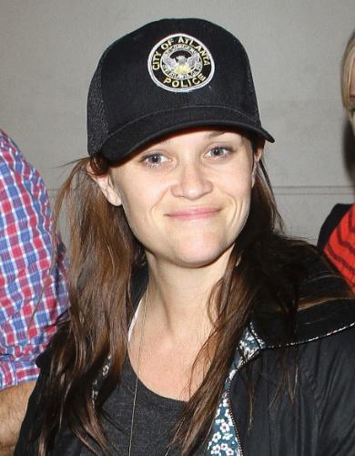 4.abr.2013 - Reese Witherspoon usa boné da polícia de Boston ao desembarcar no aeroporto de Los Angeles com a família