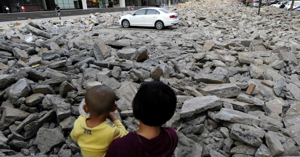 6.mai.2013 - Mulher com uma criança no colo observa carro estacionado em meio a entulhos em Taiyuan, na província de Shanxi (China), neste domingo (5). O local, onde funcionava um estacionamento, foi demolido para a ampliação de uma rua. De acordo com a agência de notícias Reuters, como o dono do veículo não foi localizado em um prazo de dez dias, funcionários foram orientados a dar início à obra, mesmo com o carro estacionado