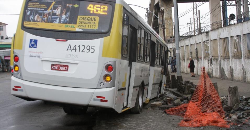 6.mai.2013 - Ônibus cai em buraco de obras em frente à rampa de acesso às estações de trem e metrô de São Cristóvão, no Rio de Janeiro (RJ), na manhã desta segunda-feira (6). O asfalto em frente ao ponto de ônibus cedeu, quando o ônibus parou. Não houve feridos