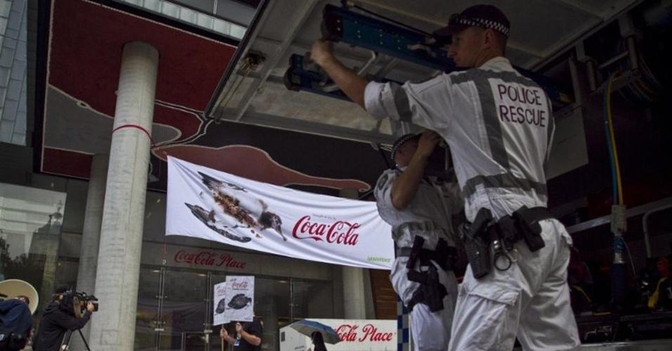 7.mai.2013 - Policiais são acionados para retirar faixa da campanha do Greenpeace estendida em frente à sede da Coca-Cola em Sydney, na Austrália. De acordo com a organização, a marca de refrigerantes está tentando barrar a implementação de um sistema nacional de reciclagem na Austrália