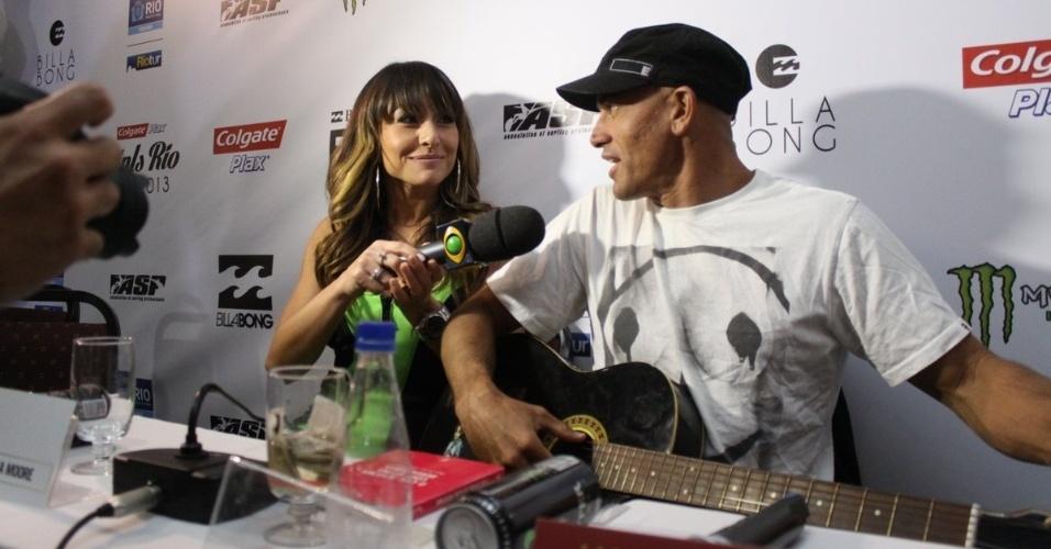 7.mai.2013 - Sabrina Sato entrega violão ao surfista Kelly Slater, ex-namorado de Gisele Bundchen, durante evento na Barra da Tijuca, no Rio de Janeiro