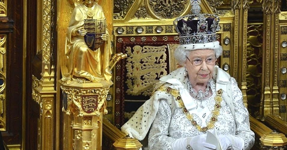 8.mai.2013 - A rainha do Reino Unido, Elizabeth 2ª, ao lado do príncipe Charles, profere seu discurso durante a cerimônia de abertura do ano legislativo do Parlamento, em Londres, nesta quarta-feira (8). O príncipe Charles participa pela primeira vez dessa cerimônia