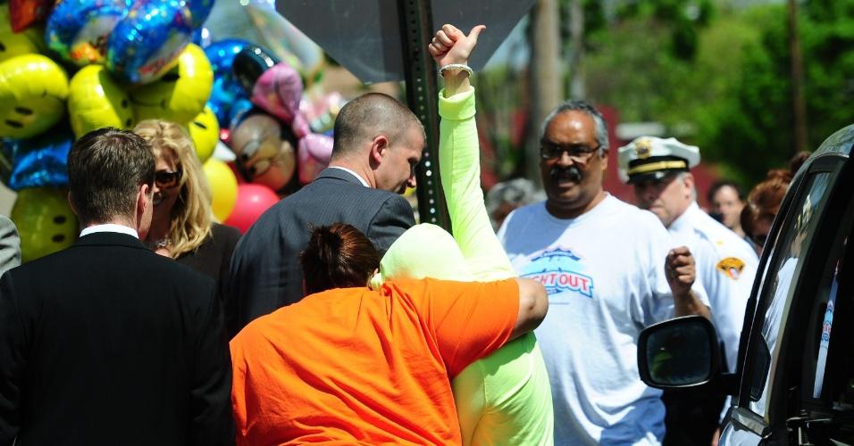 8.mai.2013 - Gina DeJesus, uma das três mulheres sequestradas e encontradas vivas após dez anos, acena para multidão ao chegar à casa de sua família em Cleveland, Ohio (EUA). A vítima evitou mostrar o rosto
