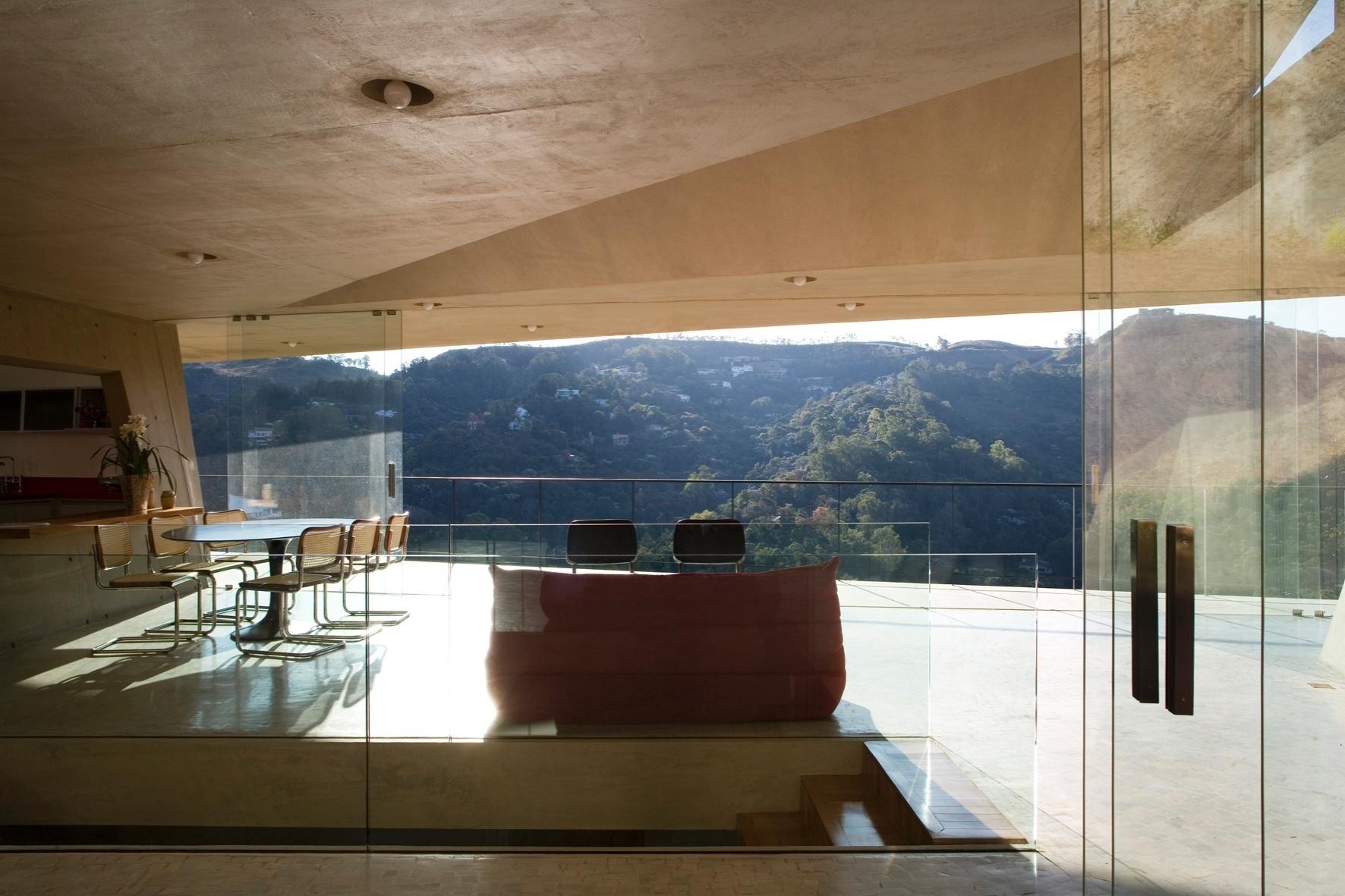A área social da Casa PL, projetada por Fernando Maculan e Pedro Morais, forma uma praça, integrada com o verde exterior a partir de fechamentos laterais em vidro temperado. Atrás do sofá, um fosso esconde a escadaria para o andar inferior e íntimo da residência