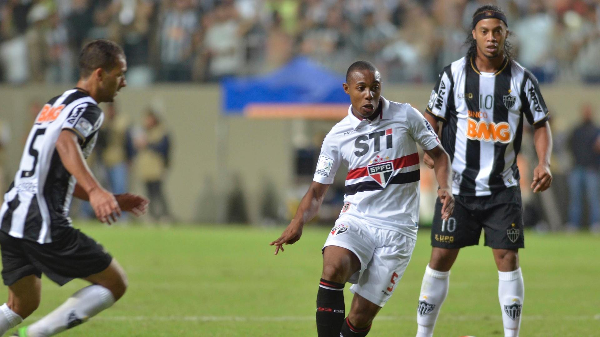 08.mai.2013 - Observado por Ronaldinho Gaúcho (dir), volante Wellington, do São Paulo, toca a bola durante a derrota por 4 a 1 para o Atlético-MG, pelas oitavas de final da Copa Libertadores