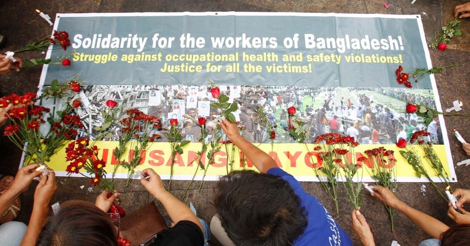 9.mai.2013 - Trabalhadores filipinos acendem velas e depositam flores em solidariedade aos trabalhadores da indústria têxtil de Bangladesh, durante protesto em Manila, nas Filipinas. Cerca de 800 trabalhadores morreram após um prédio de oito andares desabar em Savar, próximo à capital de Bangladesh, Dacca, em 24 de abril. Nesta quinta-feira (9), um incêndio em outra fábrica de roupas matou oito trabalhadores, também em Dacca