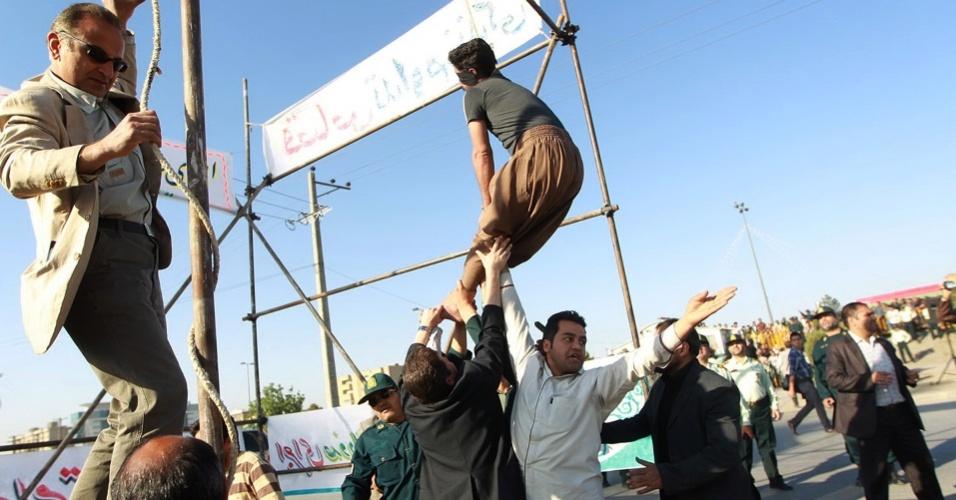 9.mai.2013 - Em foto divulgada pela agência de notícias iraniana Mehr, policiais tentam salvar homem com corda no pescoço segundos depois da execução pública de sua sentença de morte, por assassinato. O homem foi perdoado pela família da vítima no momento em que a pena estava sendo aplicada o que, segundo a lei islâmica, impede a pena de morte. Mesmo assim, não houve tempo para salvá-lo. O caso aconteceu na última quarta-feira (8), na cidade de Mashhad, no nordeste do Irã
