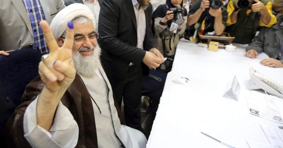 9.mai.2013 - Ex-ministro iraniano dos Serviços de Inteligência, Ali Fallahian (à esquerda) faz gesto de vitória enquanto registra nesta quinta-feira (9) sua candidatura para as próximas eleições gerais, em Teerã, no Irã. O Conselho dos Guardiões do país vai decidir até 21 de maio quais candidatos julga adequados e quais vai vetar para a campanha eleitoral rumo à eleição do dia 14 de junho