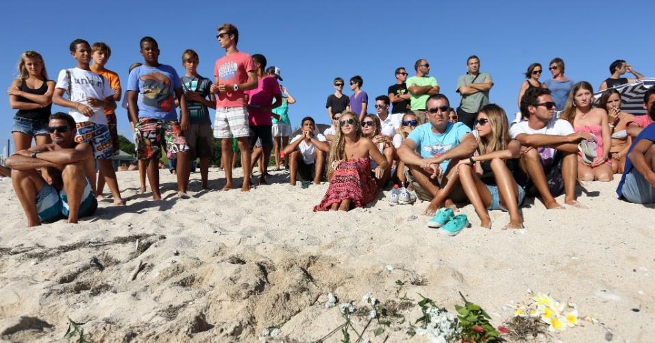 9.mai.2013 - Grupo de pessoas deposita flores na praia de Brisants, em Saint Gilles-le-Bains, oeste da França, para homenagear surfista que foi morto por um tubarão na última quarta-feira (8). O homem de 36 anos, que ainda não foi identificado, passava a lua de mel na praia francesa e foi atacado duas vezes pelo peixe, segundo a polícia local