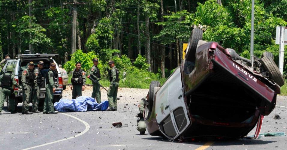 9.mai.2013 - Oficiais de segurança inspecionam destroços de carro de polícia atingido nesta quinta-feira (9) por bomba colocada em estrada da província de Yala, sul de Bangcoc, na Tailândia, supostamente por militantes muçulmanos. Três policiais se feriram, segundo a instituição