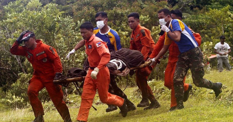9.mai.2013 - Soldados filipinos e membros do serviço de resgate transportam corpos de dois alemães falecidos durante erupção do vulcão Mayón em Mallipot