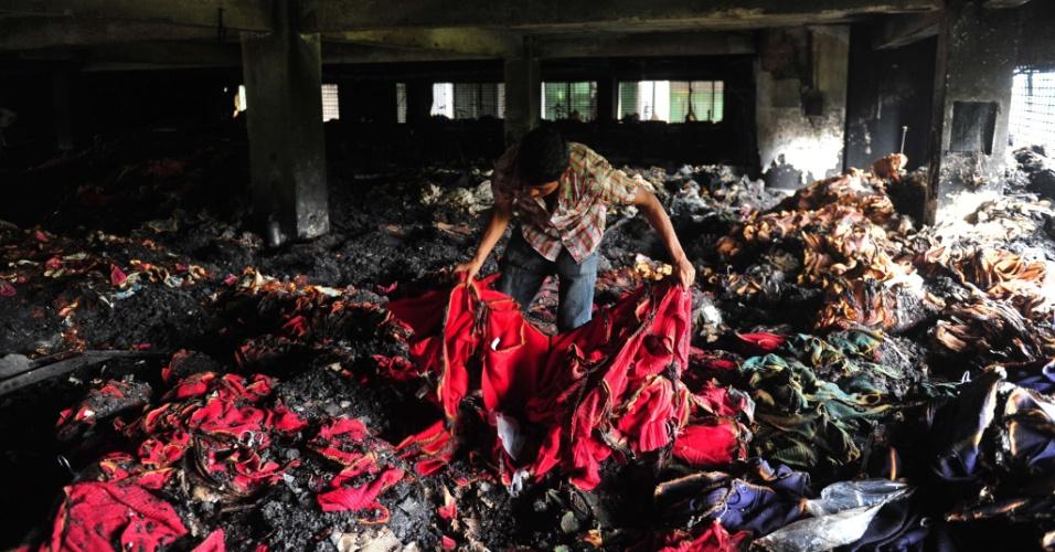 9.mai.2013 - Trabalhador recolhe roupa após incêndio em fábrica de roupas do grupo Tung Hai, no distrito industrial de Dacca, em Bangladesh, nesta quinta-feira (9). De acordo com a Reuters, ao menos oito pessoas morreram no local