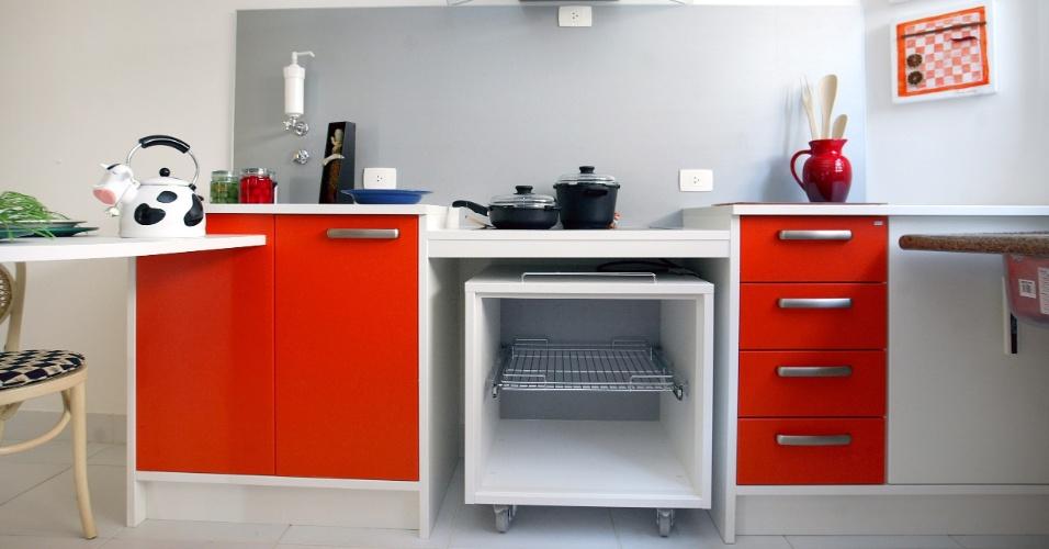 Na cozinha projetada pela arquiteta Sandra Perito, foram colocados os tampos de diferentes alturas. Note que o módulo com rodízio permite abrir espaço sob a bancada do cooktop para o cadeirante
