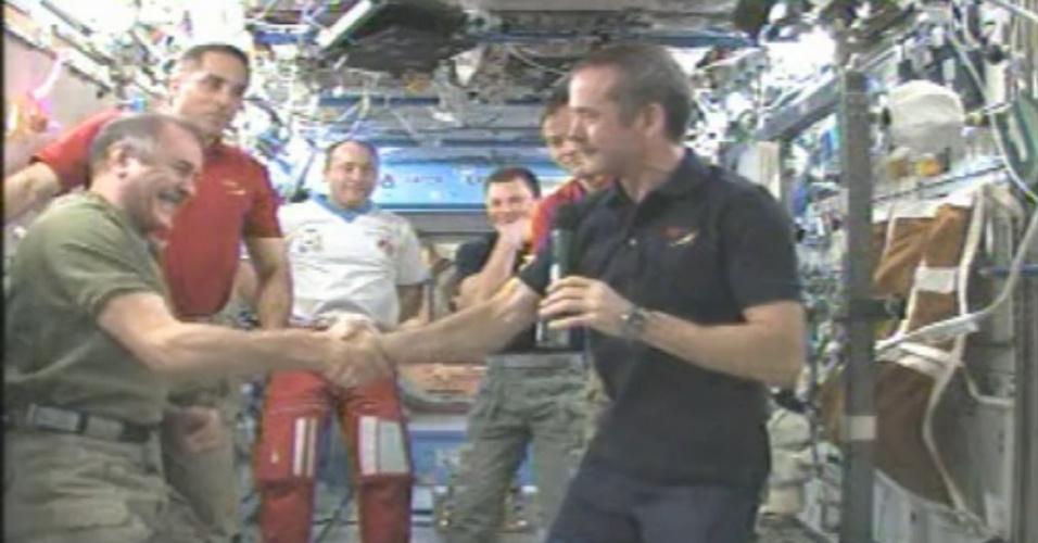12.mai.2013 - O astronauta canadense Chris Hadfield (à direita, de camiseta azul) passa o comando da Estação Espacial Internacional (ISS,  na sigla em inglês) ao cosmonauta russo Pavel Vinogradov (à esquerda, de verde), inaugurando a expedição 36. Hadfield chegou à ISS junto com o norte-americano Tom Marshburn e o russo Roman Romanenko em dezembro do ano passado - o trio deve voltar à Terra nesta segunda-feira (13), segundo previsão da Nasa (Agência Espacial Norte-Americana)