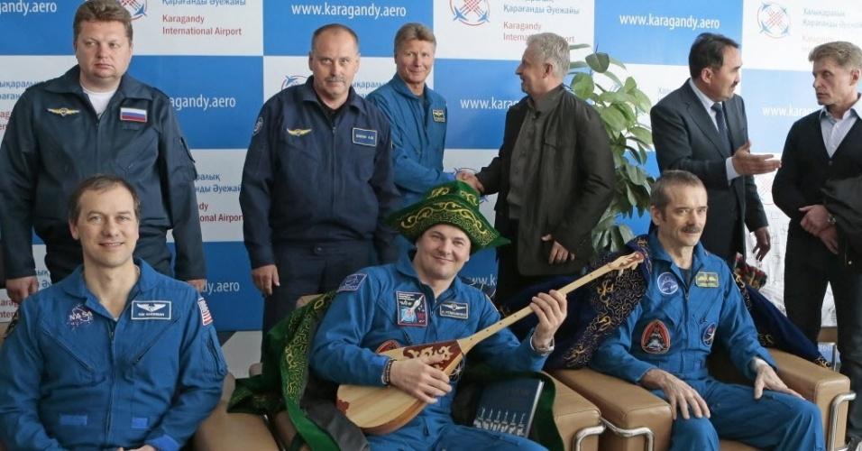 14.mai.2013 - Astronautas que passaram quase cinco meses na Estação Espacial Internacional (ISS, na sigla em inglês), na órbita da Terra, são recebidos no aeroporto com trajes típicos do Cazaquistão