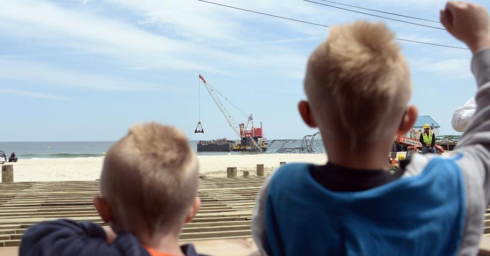 14.mai.2013 - Crianças observam montanha-russa Jet Star, em Seaside Heights, Nova Jersey (EUA), ser desmontada. Há seis meses, a tempestade Sandy destruiu as atrações do parque de diversões no Casino Pier