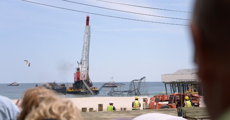 14.mai.2013 - Curiosos acompanham grua desmontar a estrutura da montanha-russa Jet Star, em Seaside Heights, Nova Jersey (EUA). Há seis meses, a tempestade Sandy destruiu as atrações do parque de diversões no Casino Pier