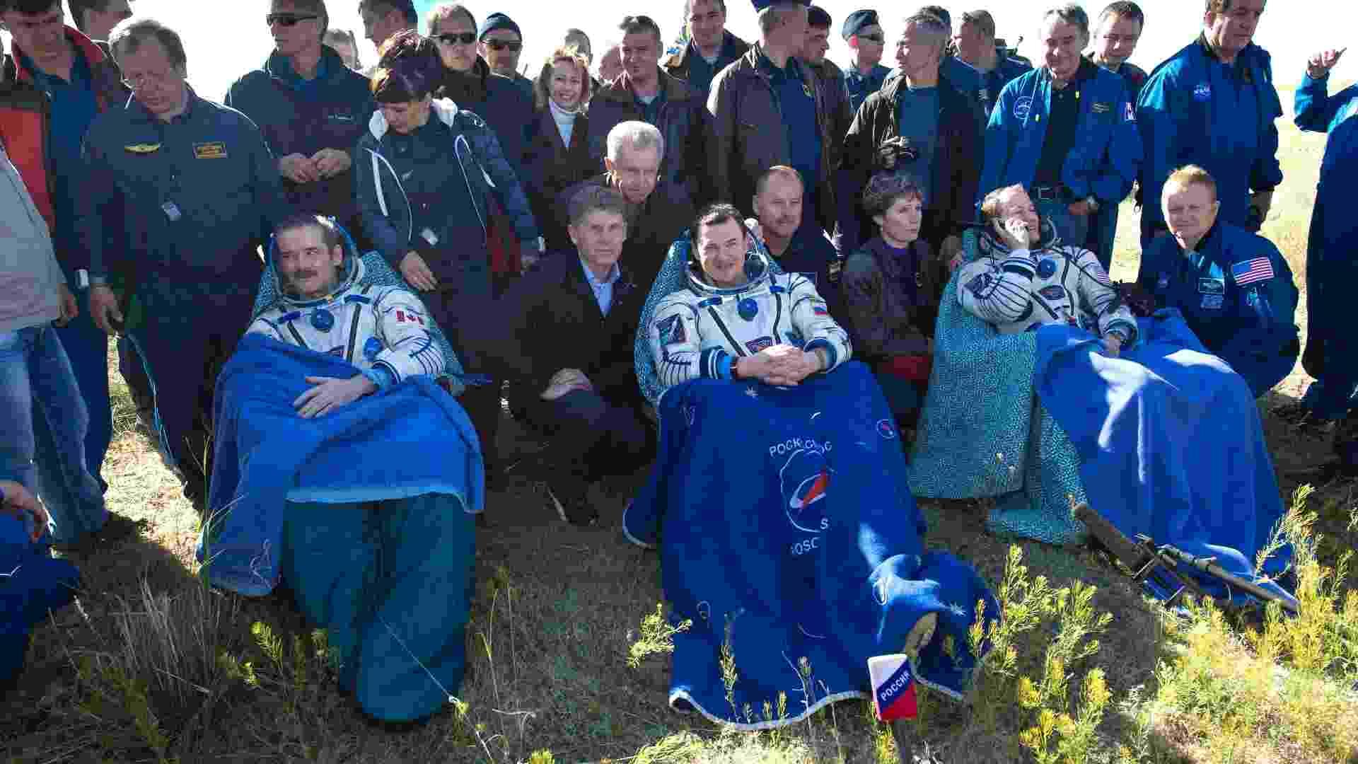 14.mai.2013 - O astronauta canadense Chris Hadfield (esq.), o norte-americano Tom Marshburn (dir.), e o cosmonauta russo Roman Romanenko (centro) descansam após deixarem a cápsula espacial russa Soyuz. O primeiro astronauta canadense a comandar uma missão na Estação Espacial Internacional trouxe a tripulação de volta à Terra, aterrissando a cerca de 150 km a sudeste da cidade de Zhezkazgan, no centro Cazaquistão, depois de passarem cinco meses no espaço - Carla Cioffi/Divulgação/Nasa/Reuters