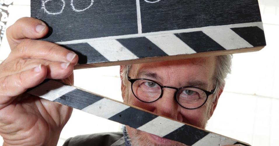14.mai.2013 - Steven Spielberg brinca com uma claquete na chegada a hotel em Cannes na véspera do festival