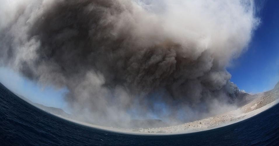 14.mai.2013 - Uma nuvem composta de gás extremamente quente, cinzas e muitas pedras, conhecida também como fluxo piroclástico, é um dos efeitos devastadores da erupção. Como ela se desloca mais rente ao chão, soltando fragmentos sólidos, essa nuvem empoeirada pode matar as pessoas. Acima, o fluxo toma o céu da ilha Montserrat, no Caribe, em registro feito com uma lente fisheye em janeiro de 2010