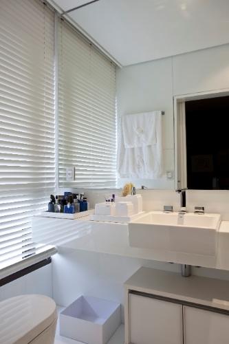 O banheiro completamente branco tem bancada Corian e revestimentos Nanoglass - material obtido por microcristalização do vidro, pó de mármore e aglutinantes, resultante da aplicação da nanotecnologia (Artimex). As louças e metais são Deca; e os acessórios da Arte e Banho