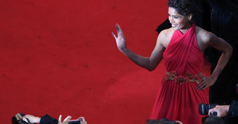 15.mai.2013 - A atriz Freida Pinto acena para os fotógrafos na chegada à abertura do Festival de Cannes 2013, na França. O evento vai até 26 de maio