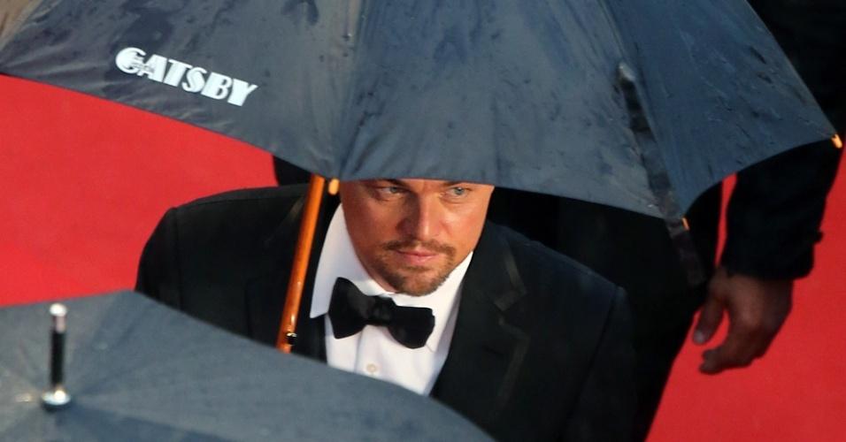 15.mai.2013 - Leonardo DiCpario protege-se da chuva ao chegar à abertura do Festival de Cannes, que teve exibição de