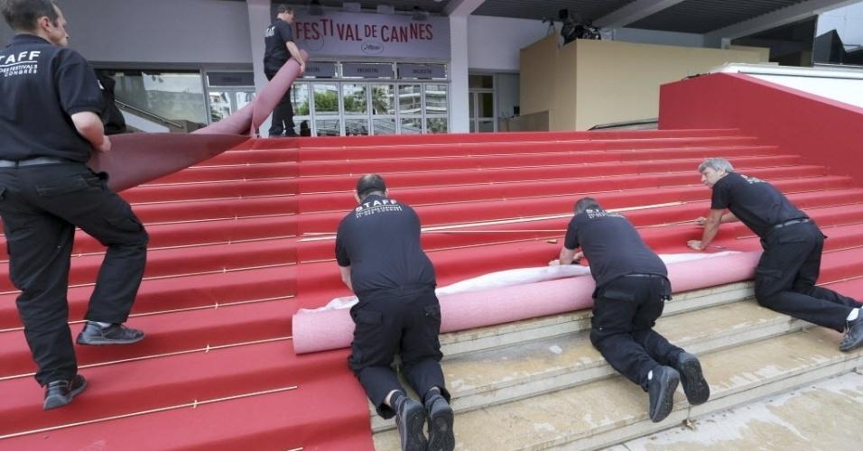 15.mai.2013 - Trabalhadores colocam o tapete vermelho na escadaria do palácio do festival