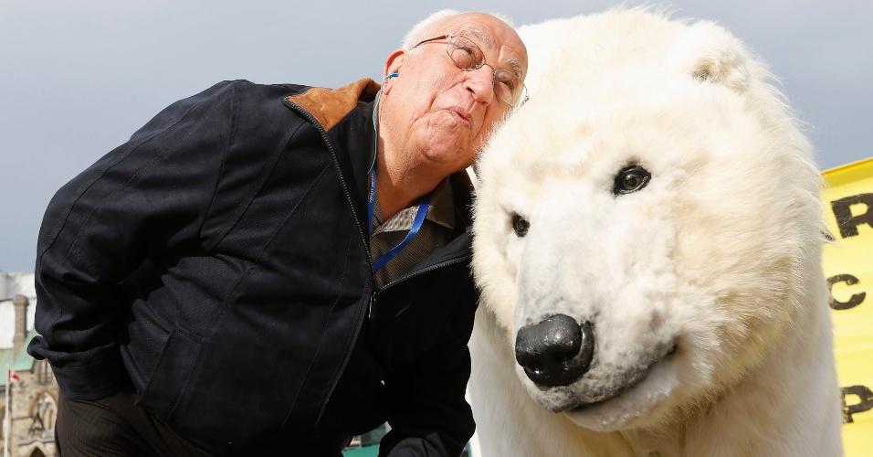 15.mai.2013 - Turista posa com ativista do Greepeace vestido de urso polar durante manifestação em frente ao Parlamento de Hill, em Ottawa, no Canadá