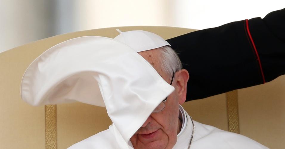 1º.mai.2013 - Mas para tentar driblar os maus ventos que o impediam de enxergar, o papa Francisco precisou de uma mãozinha durante audiência geral semanal na praça de São Pedro, no Vaticano