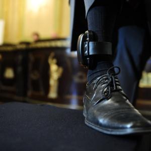 Homem mostra tornozeleira eletrônica