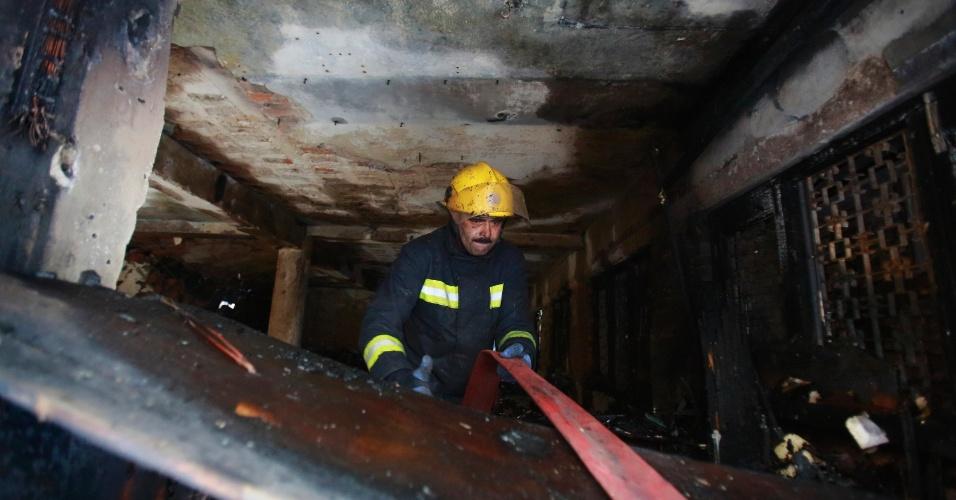 17.mai.2013 - Bombeiro puxa mangueira para dentro de casa que pegou fogo em Thamel, bairro turístico de Katmandu (Nepal