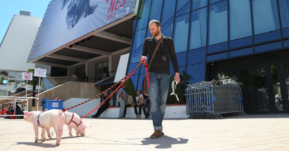 17.mai.2013 - Em frente ao Palácio dos Festivais, em Cannes, homem passeia com os porcos Violet e Pink para promover o filme