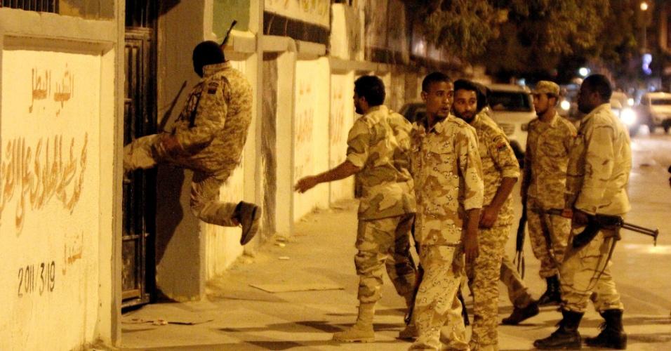 17.mai.2013 - Membros de grupo de segurança entram à força em escola durante operação em Benghazi (Líbia) para a apreensão de explosivos e prisão de suspeitos de bombardeios recentes em instalações de segurança