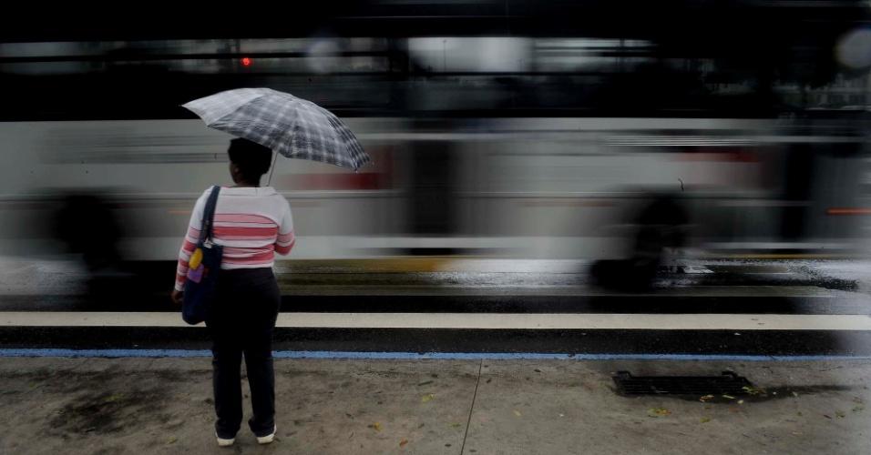 17.mai.2013 - Ônibus passa por mulher próximo à Central do Brasil, no centro do Rio de Janeiro, em dia chuvoso na cidade nesta sexta-feira (17)