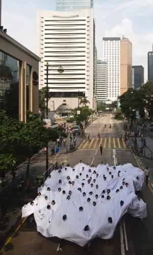 """17.mai.2013 - Pessoas de branco participam nesta sexta-feira (17) no centro financeiro de Hong Kong (China) da performance """"Divisor"""", idealizada pela artista brasileira Lygia Pape"""