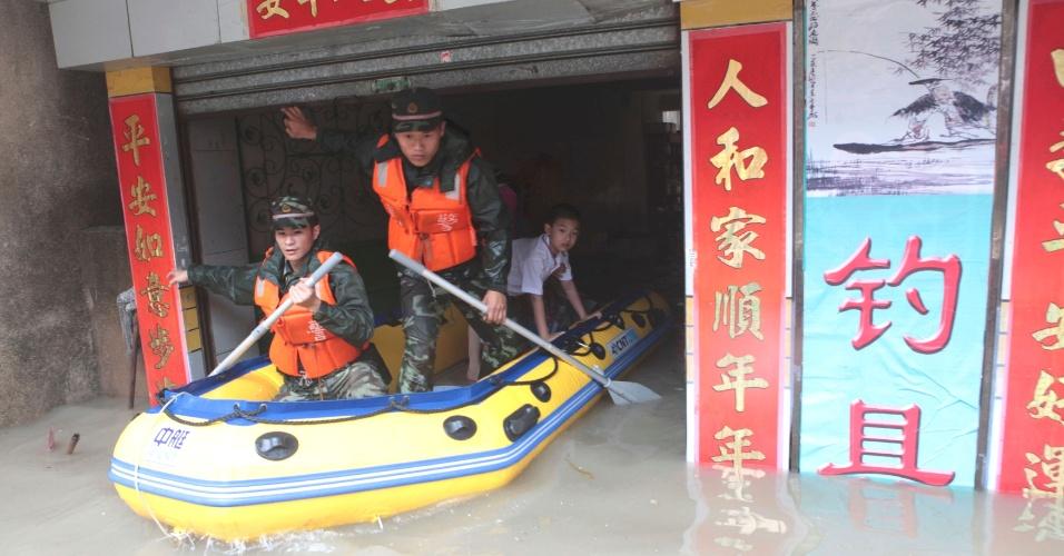 17.mai.2013 - Socorristas remam barco e retiram garoto de casa alagada em Xiamen, província de Fujian (China)