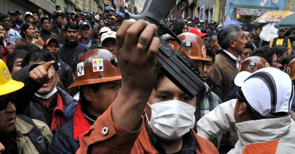17.mai.2013 - Trabalhadores mostram arma roubada de um policial durante um protesto realizado em La Paz, na Bolívia. O ato marcou o 12º dia de greve convocada pelo sindicato COB (Central Operária Boliviana). Os grevistas exigem do governo uma pensão equivalente a 100% de seus salários