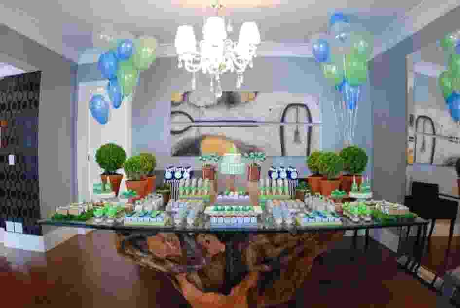"""O chá de bebê com tema """"Sapinho"""" foi montado na sala de jantar da família. As cores azul e verde deram o tom da decoração e estavam presentes nas forminhas de doces e na pasta americana que confeitou algumas guloseimas, incluindo o bolo. Bexigas de gás hélio foram amarradas aos buchinhos nas extremidades da mesa. http://www.atelierdefestas.com - Divulgação"""