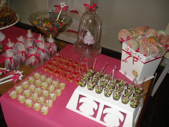 Para decorar a mesa de doces, maçãs do amor e pirulitos foram embrulhados em pedaços de tule. Já os copinhos de doce ganharam lacinhos de cetim. www.aartedebemreceber.blogspot.com