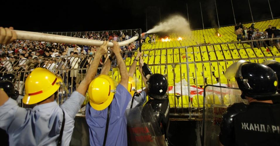 18.mai.2013 - Bombeiros tentam apagar incêndio causado por torcedores do Estrela Vermelha durante clássico contra o Partizan, pelo Campeonato Sérvio