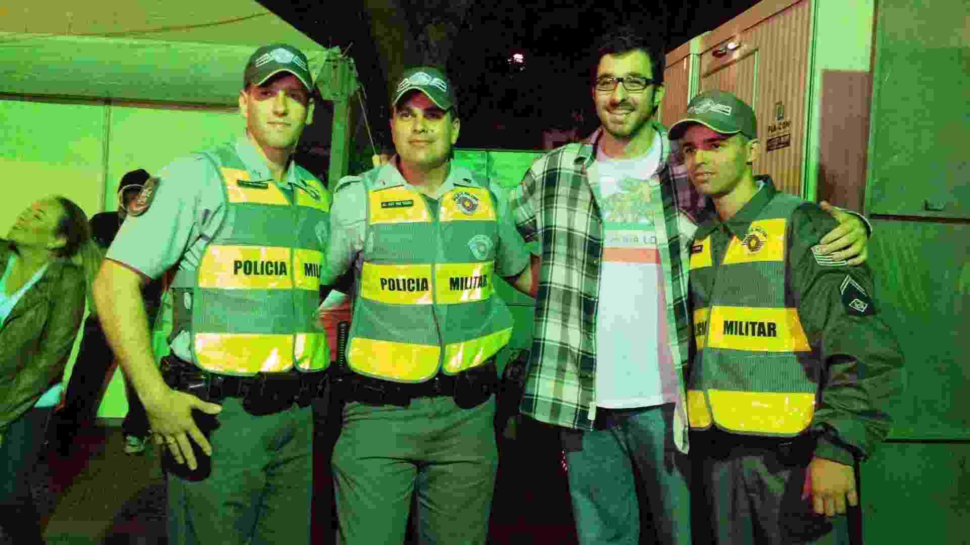 18.mai.2013 - Policiais tietam o humorista Rafinha Bastos antes de sua apresentação no Palco Sé da Virada Cultural 2013 - Adriana de Barros/UOL