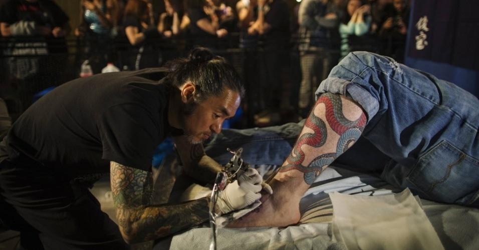18.mai.2013 - Tatuador desenha serpente na perna de um participante de evento sobre tatuagem em Nova York